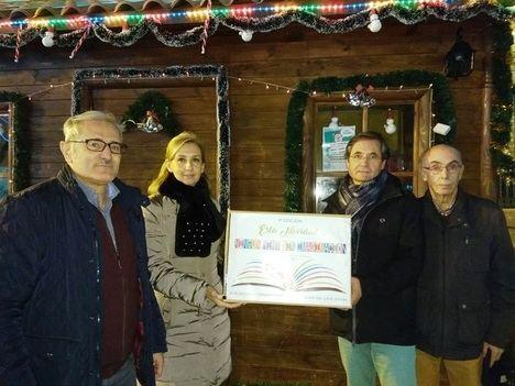 Luis Miguel Román presidente de la Sociedad Cervantina hace entrega a Milagros Plaza,  representante de El Sosiego, de una de  las cajas de libros recogidos
