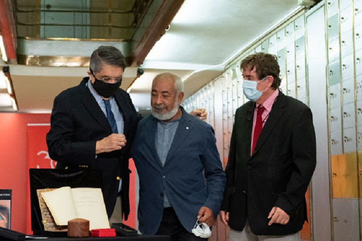 Sergio Ramírez (izda) y Leonardo Padura de abrazan en la Caja de las Letras, en presencia del director del Instituto Cervantes, Luis García Montero